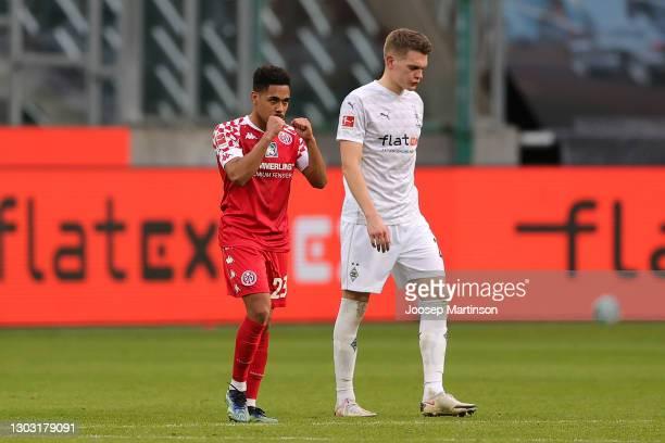 Phillipp Mwene of 1. FSV Mainz 05 celebrates following his team's victory, as Matthias Ginter of Borussia Moenchengladbach looks dejected following...