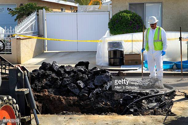 Phillips 66 contractor pauses while cleaning up an oil spill that is contained to a 20' x 50' area that has closed the 1200 block of North Neptune...
