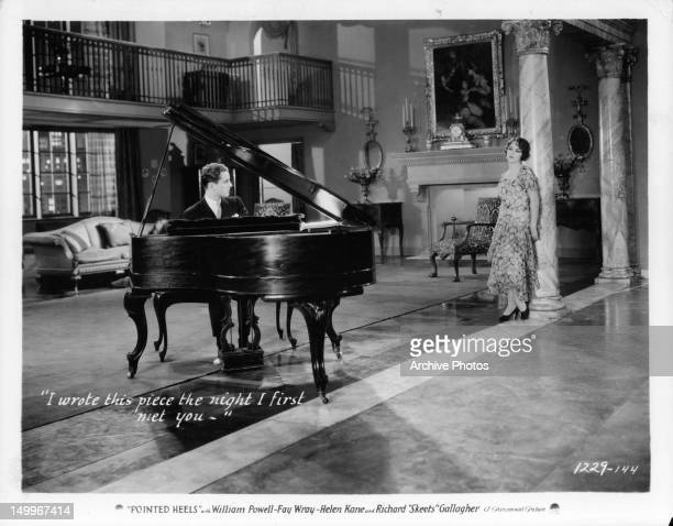 Phillips Holmes playing the piano before Fay Wray in a scene from the film 'Pointed Heels' 1929