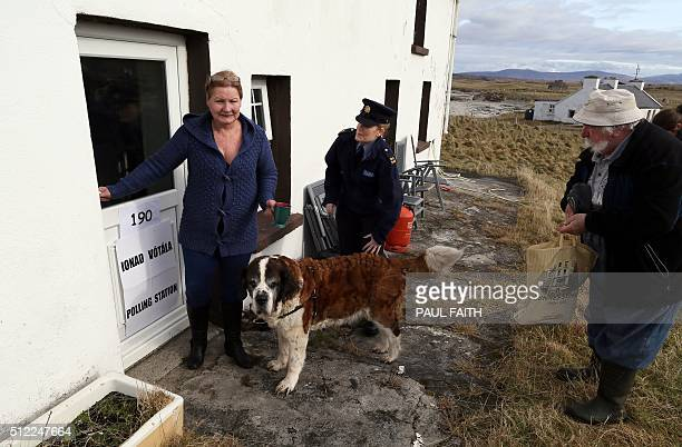 Philomena Curruid a resident of Inishfree Island speaks with fellow resident Hans Schleweck and police officer Margaret Byrne outside her home which...