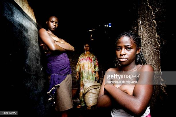 Philomene prepares to iron the breasts of two of her daughters Marianne and Carine with a hot stone which has been heated in the oven In Cameroon...