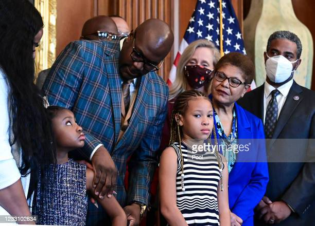 Philonise Floyd, George Floyd's brother, looks down at Gianna Floyd, George Floyd's daughter, while while standing with members of the Floyd family...