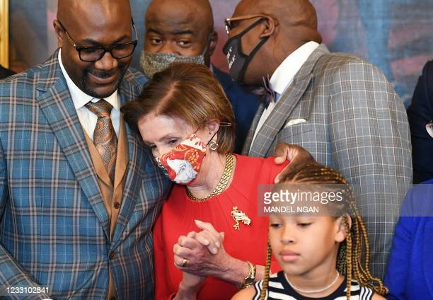Philonise Floyd, the brother of George Floyd, puts his arm around House Speaker Nancy Pelosi, D-CA, as he and other members of the Floyd family meet...