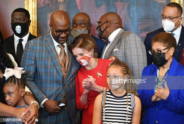 Philonise Floyd, the brother of George Floyd, puts his arms around House Speaker Nancy Pelosi, D-CA, as Rep Karen Bass , D-CA, looks on as he and...