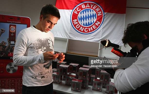 Philpp Lahm looks on the new Bayern Munich Sony Ericsson Mobile Phone at Bayern's training ground Saebener Strasse on November 22 2007 in Munich...