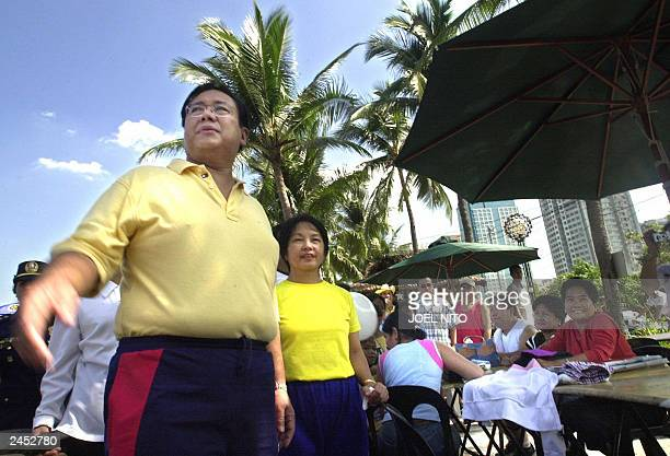 Philppine President Gloria Arroyo and her husband Jose Miguel Arroyo take a stroll along the breakwater on Roxas Boulevard in Manila 29 June 2003 as...