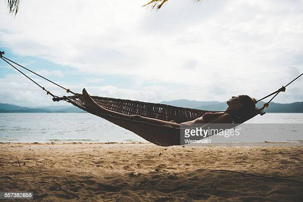 Philppines, Visayas, Woman wearing bikini relaxing on a hammock in the evening