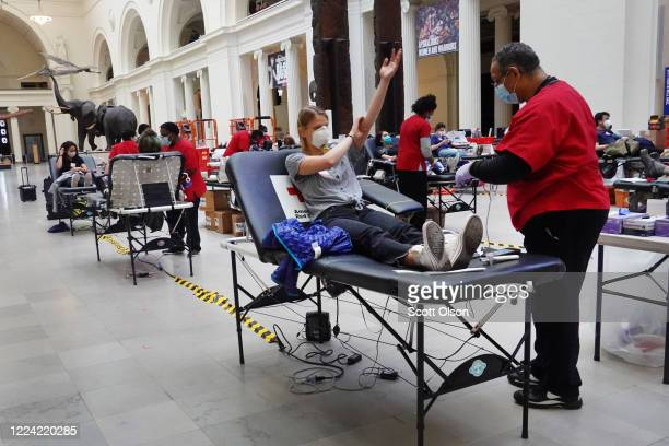 Phlebotomist Herbert Collins draws blood from Victoria Reese during an American Red Cross blood drive held at the Field Museum of Natural History on...