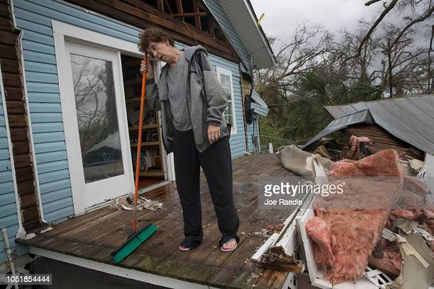 Phlomena Telker stands on what was her covered porch after hurricane Michael tore the roof of her home as it passed through the area on October 10...
