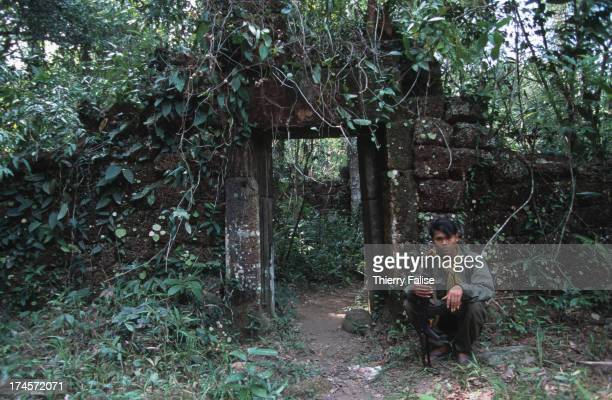 Phnom Kulen North of Angkor Wat temples A soldier sitting in front of the entrance of a IXth century temple