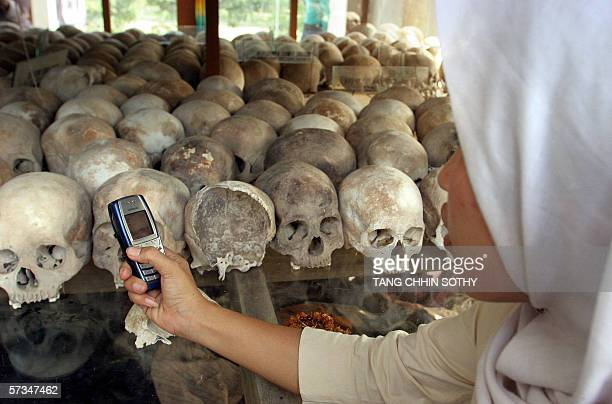 A CambodianMuslim woman takes photographs with her mobile phone of thousands of skulls on display at the Choeung Ek killing fields memorial some 15...