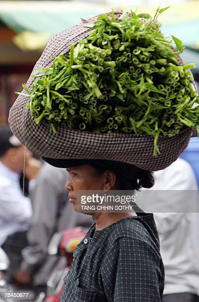 Vendor carries vegetable for sale at a market in Phnom Penh, 17 July 2007. The gap between rich and poor in Cambodia is widening at an alarming rate,...