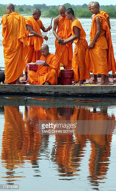 Cambodian buddhist monks prepare offerings on a boat during a ceremony which is held one day after the Pchum Ben festival on a the lake near Phnom...