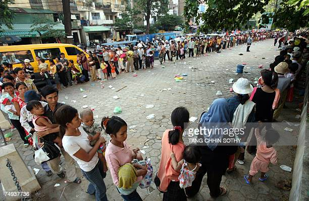 Cambodian mothers form a line as they carry their children in front of Kantha Bopha hospital in Phnom Penh 19 June 2007 Saing Ratha lies...