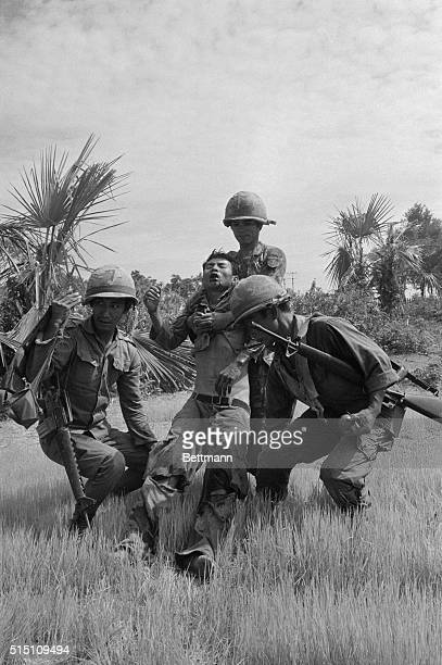 Cambodian troops carry a wounded buddy to a rear position during a firefight with Khmer Rouge forces along HighwayFive 11 miles northwest of Phnom...