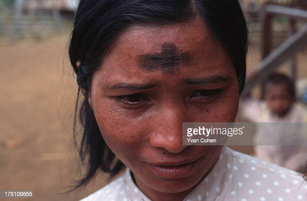 Phnong montagnard woman shows off her faith by marking a black cross on her forehead Traditionally animist a small number of Phnong have converted to...