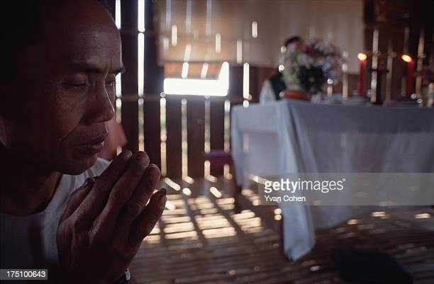 Phnong tribesman joins his hands in a gesture of a prayer during a catholic mass at a tiny bamboo church in northeastern Cambodia A small group of...