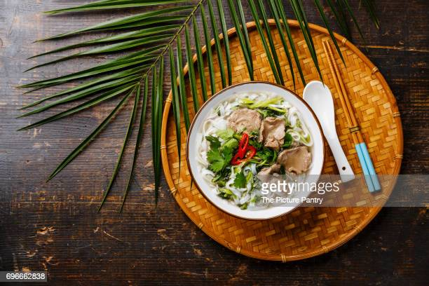 Pho Bo vietnamese Soup with beef on bamboo tray on wooden background