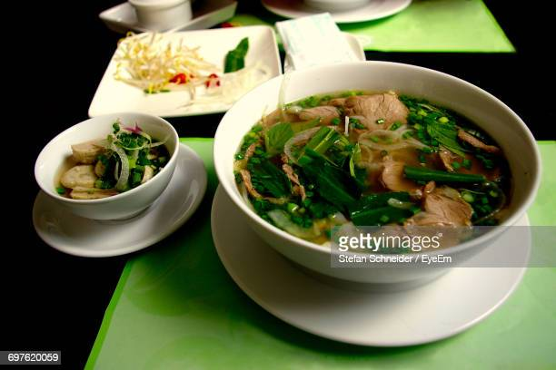 Pho Soup In Bowls On Plate Over Table