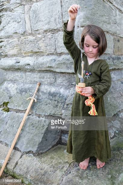 Phoebe Kirkham from Newport Pagnell spins wool as she attends the Viking Festival at Whitby Abbey on August 24 2019 in Whitby England Temperatures...