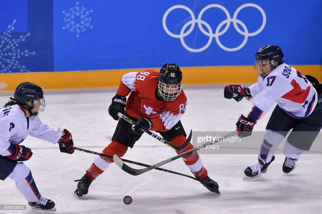 TOPSHOT - Phoebe Staenz (C) of Switzerland evades a tackle from Choi Ji-yeon (R) of Unified Korea during their women's Classifications ice hockey game of the Pyeongchang 2018 Winter Olympic Games at the Kwandong Hockey Centre in Gangneung on February 18, 2018. / AFP PHOTO / Ed JONES