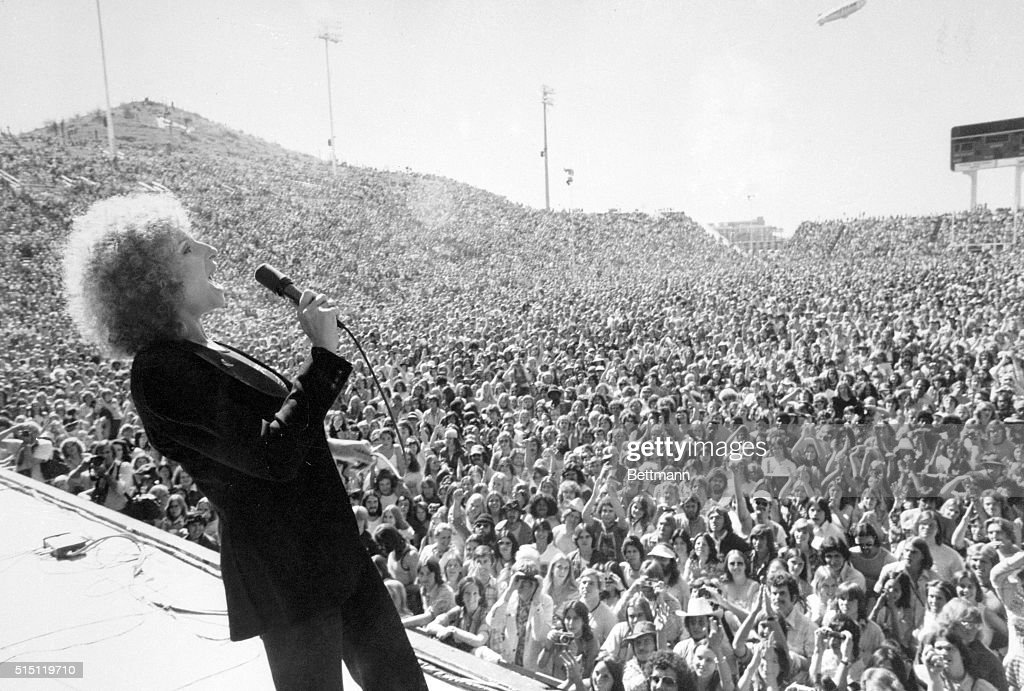Barbra Streisand, actress, shown performing to young crowd at Phoenix Tempe Football Stadium in movie A Star is Born.