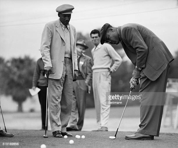 Phoenix, AZ- Joe Louis, retired World Heavyweight champion, tries out a new putter just aquired by his protege Bill Spiller who was admitted to the...