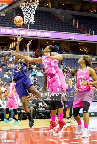 Phoenix Mercury forward Camille Little throws off balance past Washington Mystics center Krystal Thomas during a WNBA game on August 18 between the...