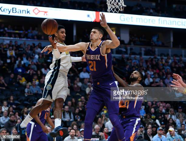 Phoenix Suns center Alex Len right blocks a layup attempt by Nuggets guard Gary Harris left during the first half of NBA game at Pepsi Center on...