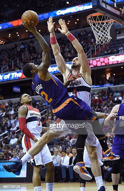 Phoenix Suns guard Eric Bledsoe tries to shoot over Washington Wizards center Marcin Gortat during the first half of their game played at the Verizon...
