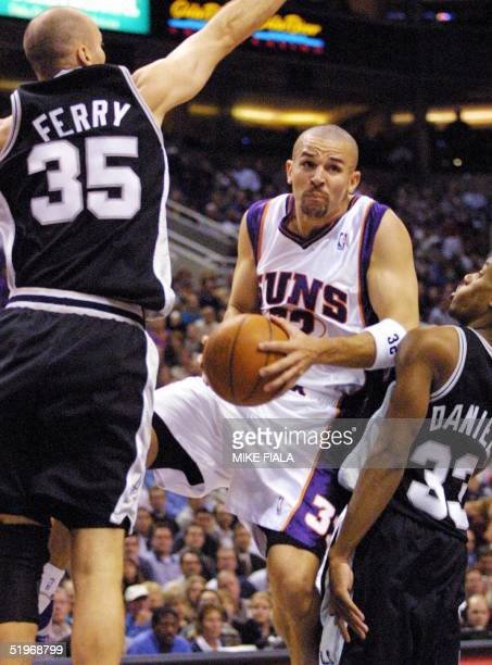 Phoenix Suns guard Jason Kidd drives to the basket as San Antonio Spurs forward Danny Ferry and guard Antonio Daniels defend during the first quarter...