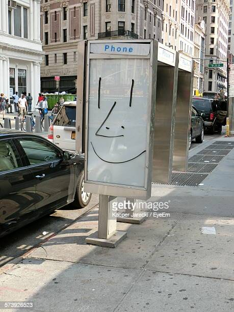 phone booth on footpath by street against buildings - telephone booth stock pictures, royalty-free photos & images