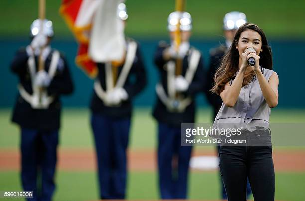Phone Haron of Grapevine sings the National Anthem as UTA's color guard presents the flags before a baseball game between the Cleveland Indians and...