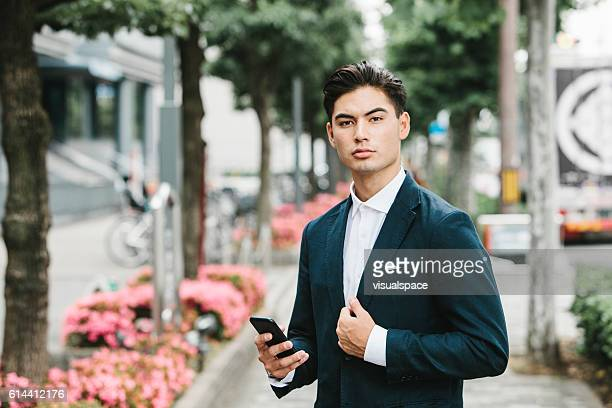 phone in the hands of an asian businessman - ハンサム ストックフォトと画像