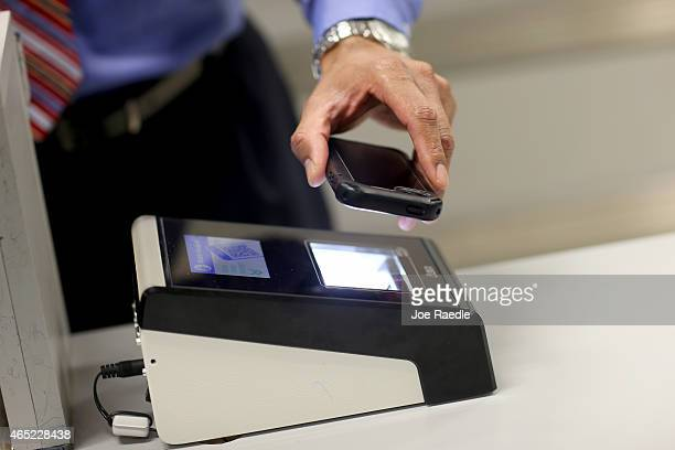 A phone is passed over a scanner during a demonstration in the use of the new mobile app for expedited passport and customer screening being unveiled...