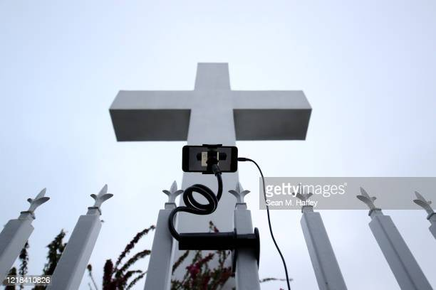 A phone is used to record a large cross during a sunrise Easter service at Mt Helix Park on April 12 2020 in San Diego California Due to fears of the...