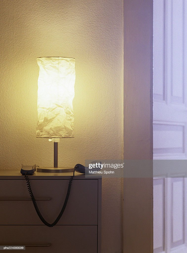Phone off hook on top of chest of drawers. : Stockfoto
