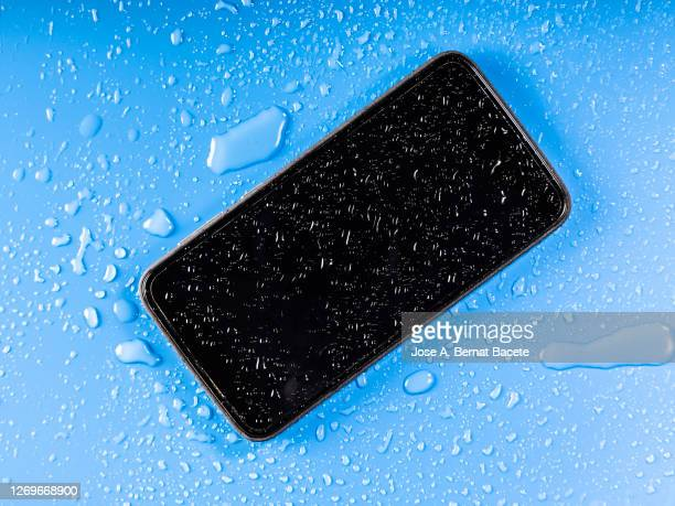 phone on the ground that is damaged by water on a blue background. - wet stock pictures, royalty-free photos & images