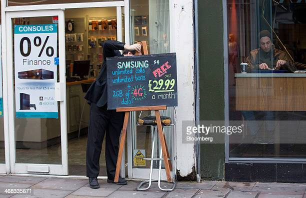 A phone shop employee adjusts a hand written sign advertising a Samsung smartphone mobile contract outside a store in Croydon south London UK on...