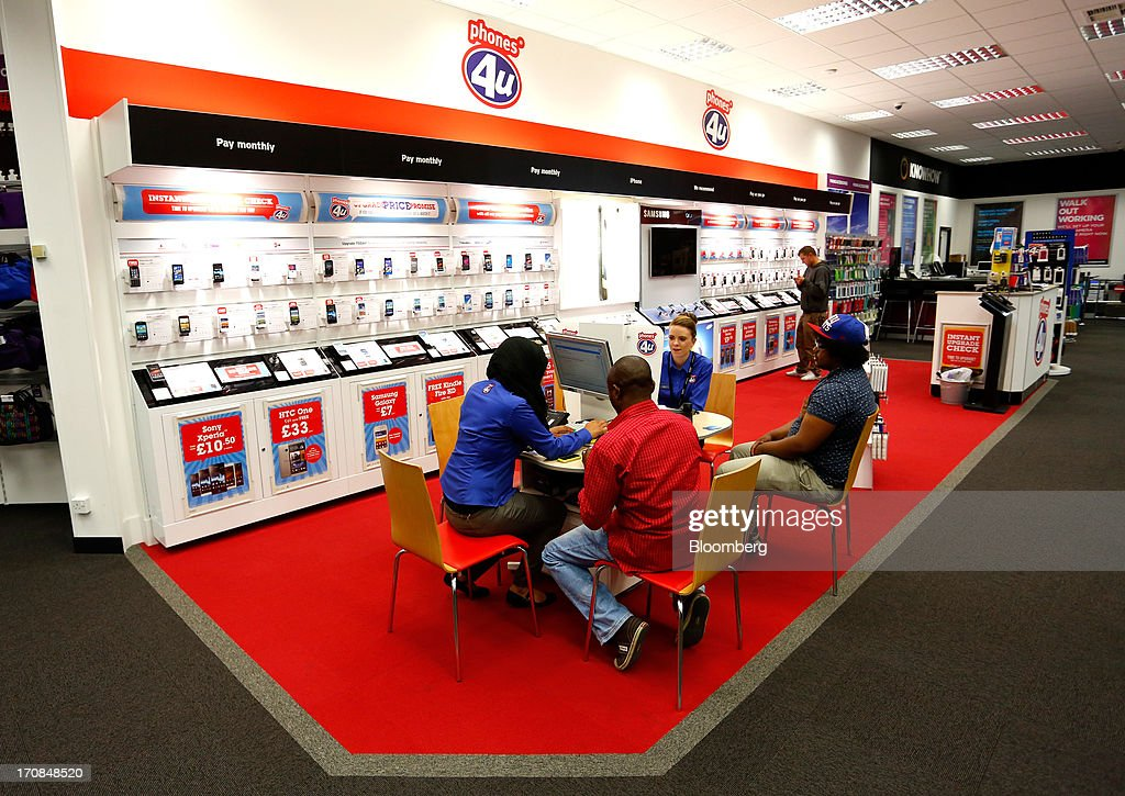 Phones 4u Ltd. employees talk with customers inside a Currys and PC World 2 in 1 store, operated by Dixons Retail Plc, in Manchester, U.K., on Tuesday, June 18, 2013. Dixons Retail Plc, the U.K.'s largest consumer-electronics retailer, said last month it will report annual pretax profit at the 'top end' of analysts' predictions after fourth-quarter revenue beat estimates on increased sales of tablets and services such as software tutorials. Photographer: Paul Thomas/Bloomberg via Getty Images