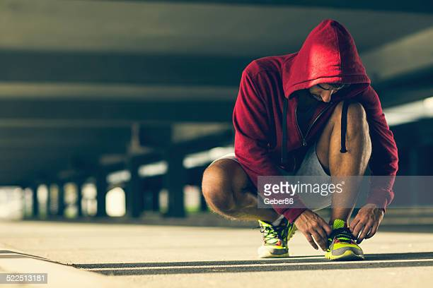 Photo af an athletic man tying his shoelace