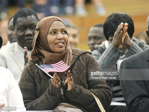 Photo by John Patriquin/Staff Photographer In top photo Suad Abrar originally from Somalia and now from Lewiston applauds others during the ceremony...
