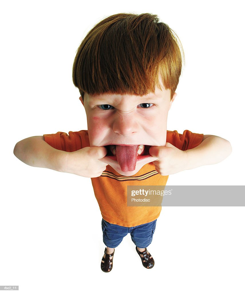 photo caricature from a birdseye view of a little boy making a silly face by pulling on his checks and sticking his tongue out : Stockfoto