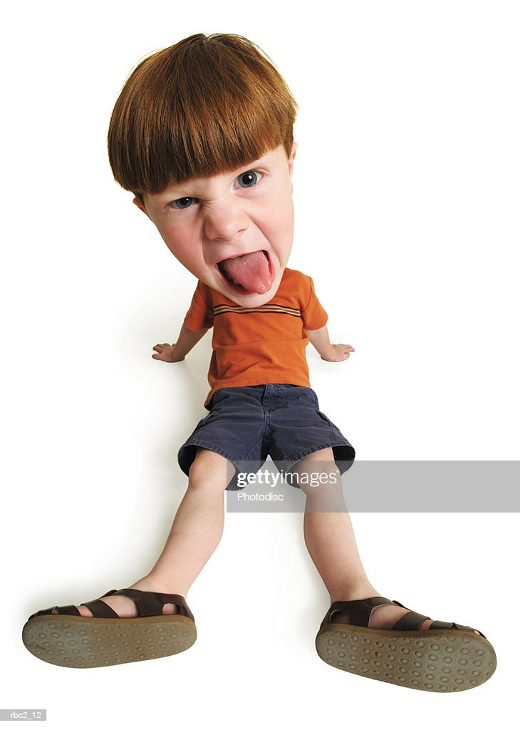 photo caricature from a birdseye view of a little boy sitting on the ground and pulling a silly face with his tongue sticking out : Stockfoto