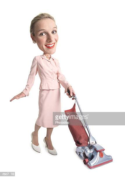 photo caricature of a caucasian woman dressed as a retro 1950 housewife as she vacuums