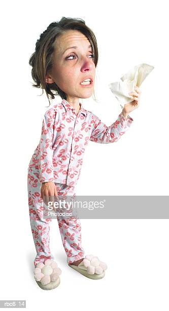 photo caricature of a caucasian woman in pink pajamas who is sick and about to sneeze into a hankerchief