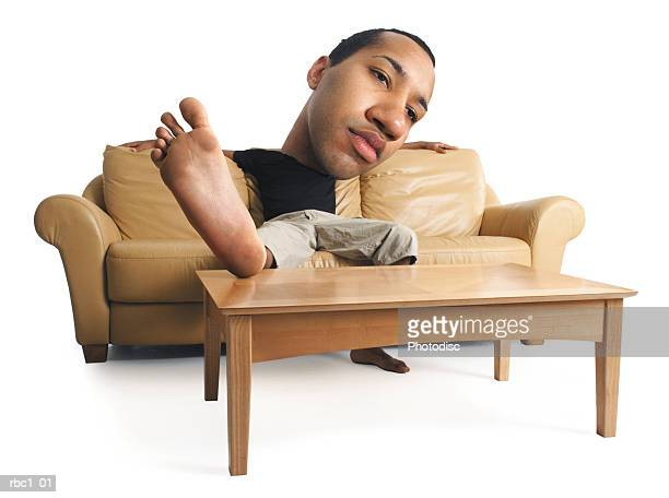 photo caricature of a young african american male in a black t-shirt stretching out and relaxing on a sofa - big foot stock photos and pictures