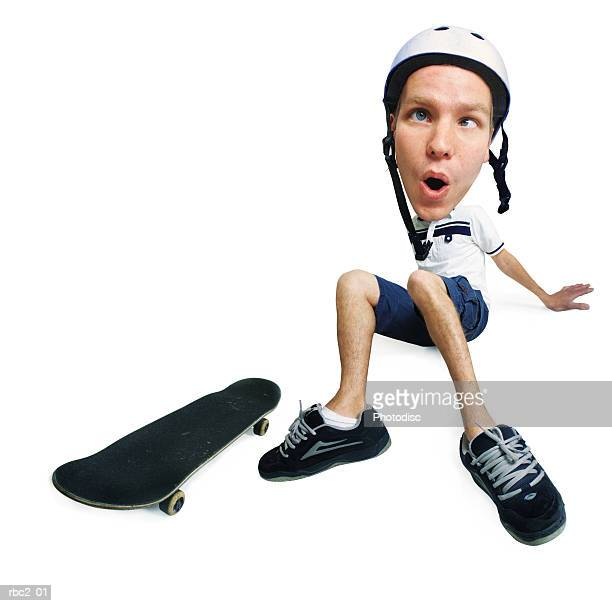 photo caricature of a young caucasian male skateboarder who has fallen off his board and sitting on the ground dizzy