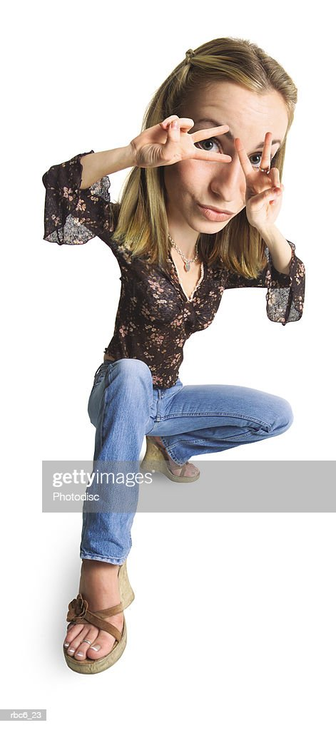 photo caricature of a young caucasian woman in jeans and a brown top as she holds her fingers over her eyes : Stockfoto
