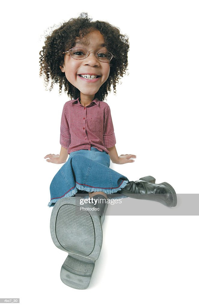 photo caricature of a young cute african american girl dressed in a jean skirt and red shirt as she sits and smiles : Stockfoto
